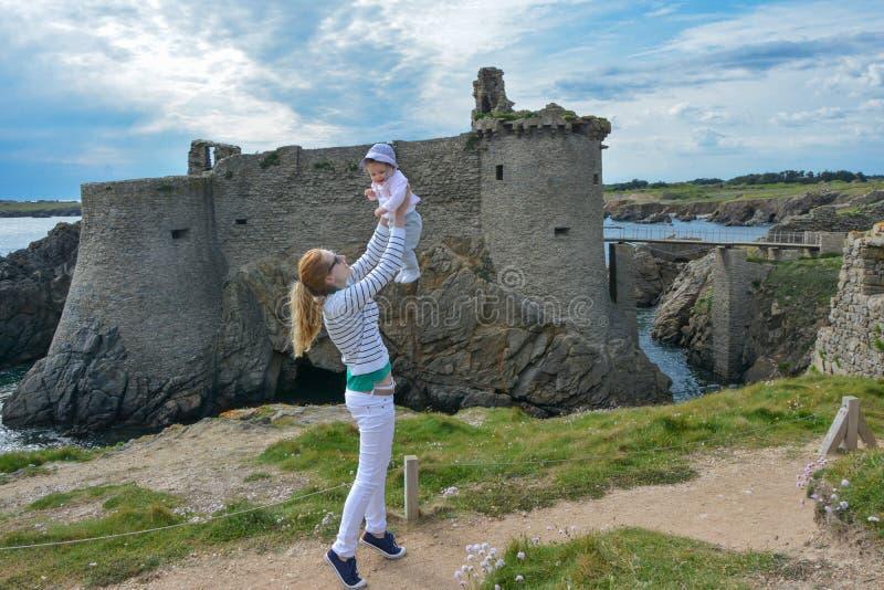 La madre lanza a su hija en el cielo cerca del castillo de la isla Yeu, Francia imagenes de archivo
