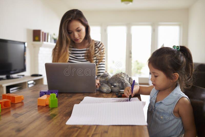 La madre lavora al computer portatile mentre la figlia disegna l'immagine in libro immagini stock