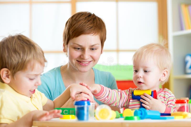 La madre le enseña a niños a trabajar con los juguetes coloridos de la arcilla del juego fotografía de archivo