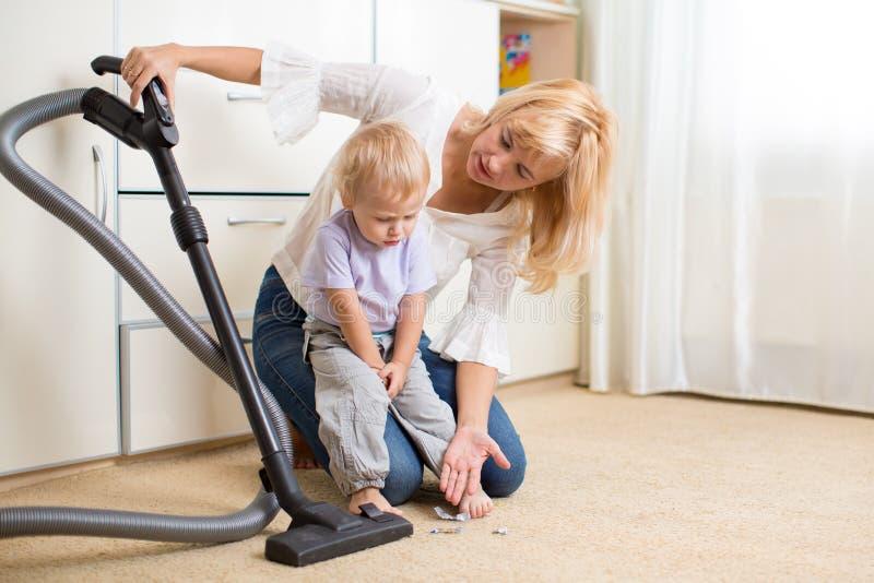 La madre le insegna la pulizia della stanza del figlio del bambino immagini stock libere da diritti