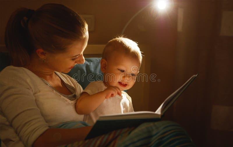 La madre lee al libro del bebé en cama fotografía de archivo libre de regalías