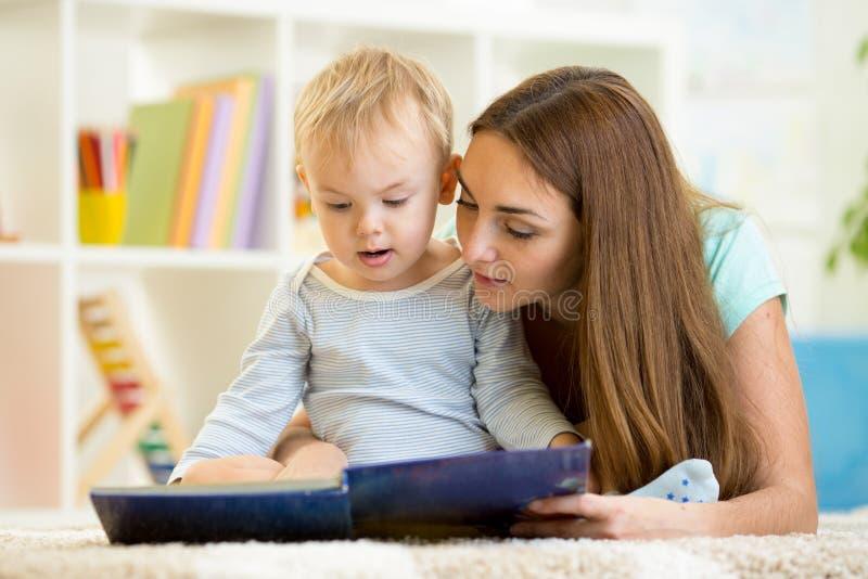 La madre legge un libro per scherzare a casa fotografie stock