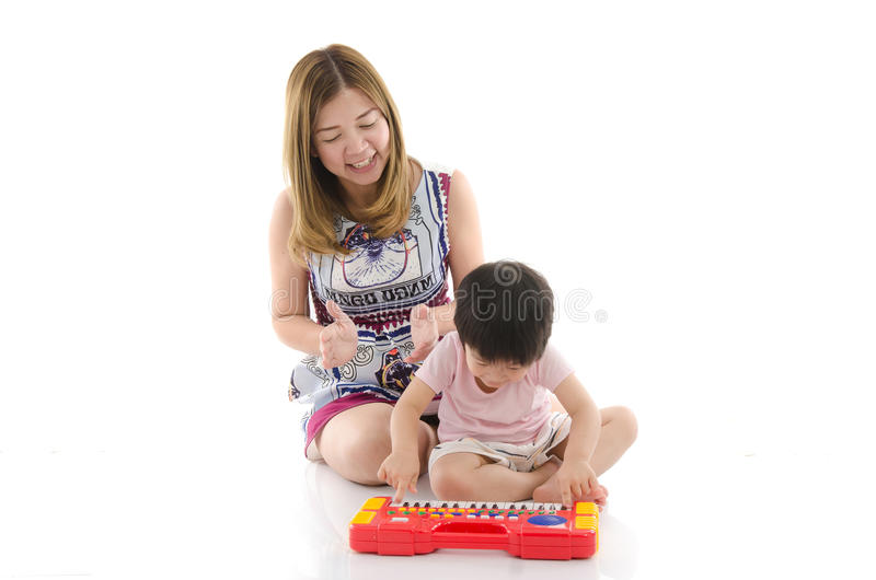 La madre linda enseña a su niño del hijo a jugar el piano eléctrico del juguete imagen de archivo libre de regalías