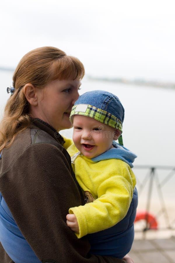 La madre lleva al bebé en honda foto de archivo