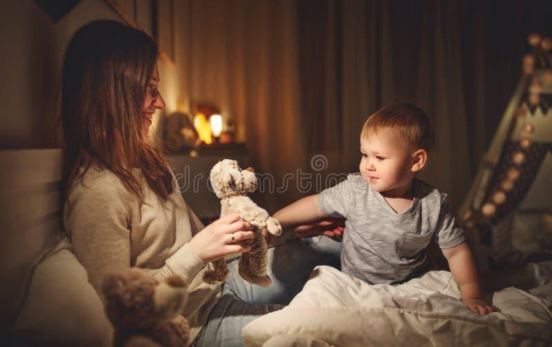 La madre mette il figlio del bambino per dormire nell'uguagliare a letto fotografie stock