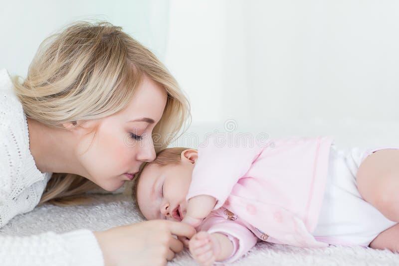 La madre mette sua figlia del bambino per dormire fotografia stock libera da diritti