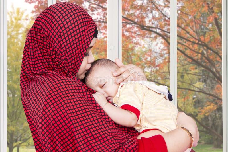 La madre musulmán calma a su bebé en casa fotos de archivo libres de regalías