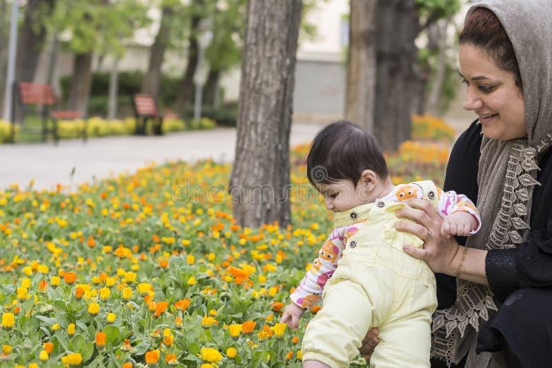 La madre musulmana che tiene il piccolo bambino dentro la molla fiorisce al parco, immagini stock libere da diritti