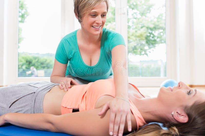 La madre nel corso della ginnastica ottiene il massaggio di recupero di gravidanza immagine stock