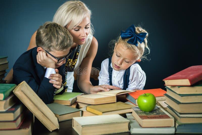La madre o el profesor que ayuda para la escuela embroma hacer la preparación, leyendo imágenes de archivo libres de regalías