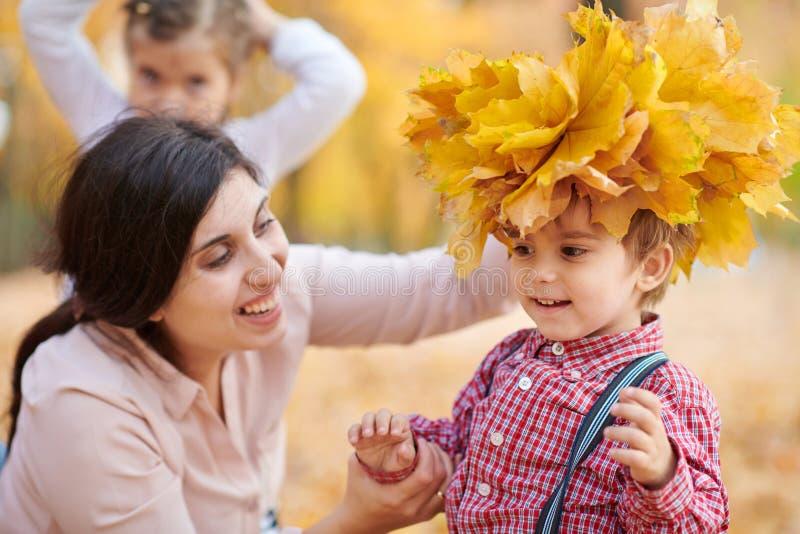 La madre pone las hojas caidas amarillas en la cabeza del hijo La familia feliz está en parque de la ciudad del otoño Niños y pad imagen de archivo