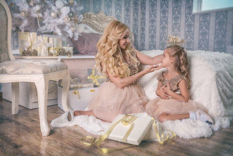 La madre pone una tiara en su cabeza del ` s de la hija en la Navidad fotos de archivo