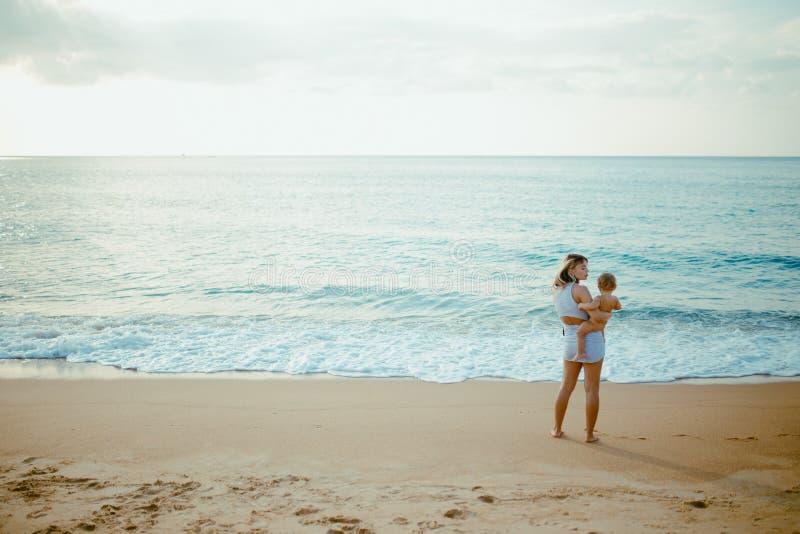 La madre porta il bambino sulla spiaggia fotografie stock libere da diritti