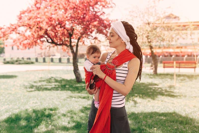 La madre porta un bambino infantile in imbracatura dell'involucro in parco primavera Concetto del parenting naturale fotografia stock libera da diritti