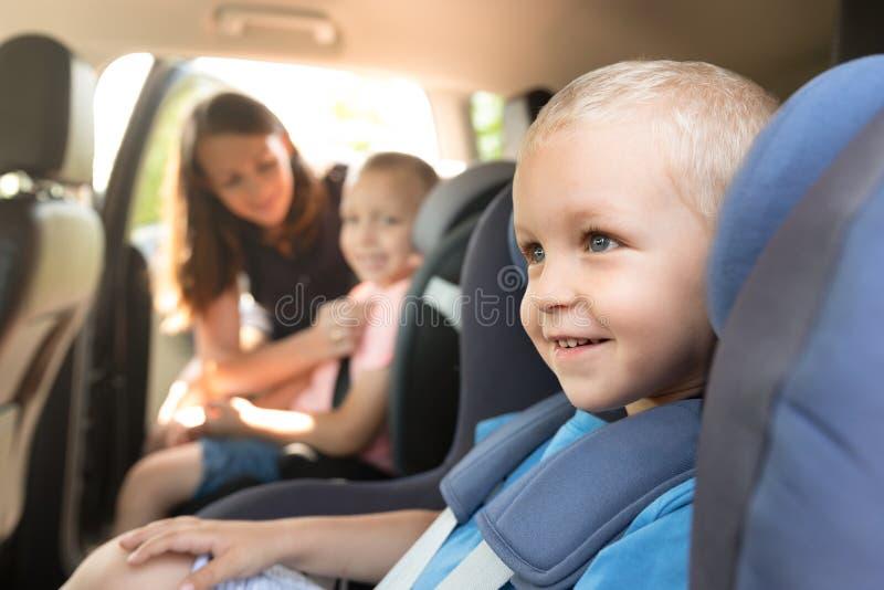 La madre prende la cura circa i suoi bambini in un'automobile fotografie stock libere da diritti