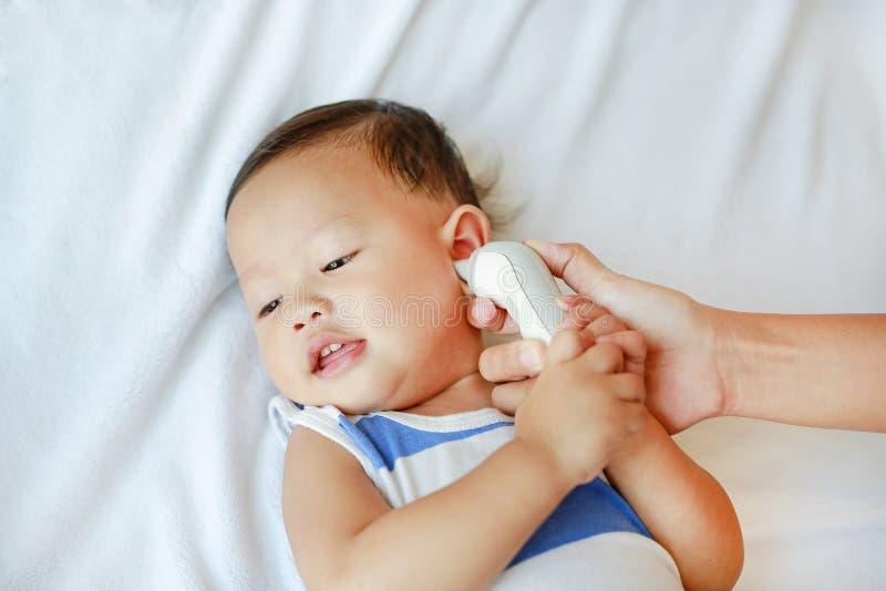 La madre prende la temperatura per il neonato con il termometro di orecchio sul letto a casa fotografia stock