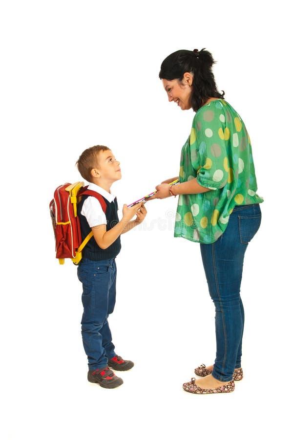 La madre prepara al muchacho para la escuela fotografía de archivo libre de regalías
