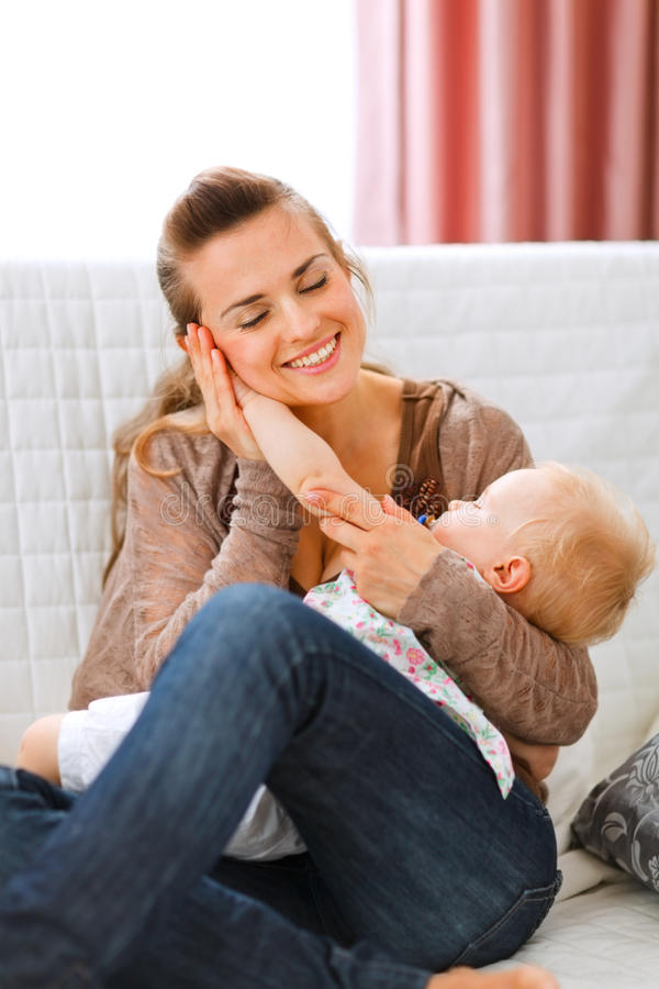 La madre puso la mano del bebé a su mejilla imagen de archivo libre de regalías