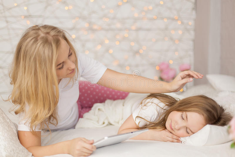 La madre puso a su hija para dormir con la tableta Interior Cuidado del concepto imágenes de archivo libres de regalías