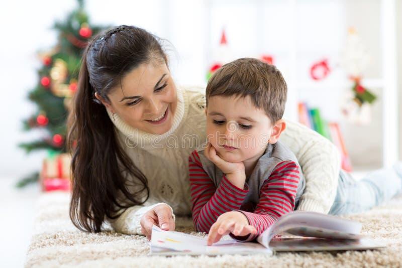 La madre que cuida lee a su niño un libro interesante el Nochebuena fotografía de archivo