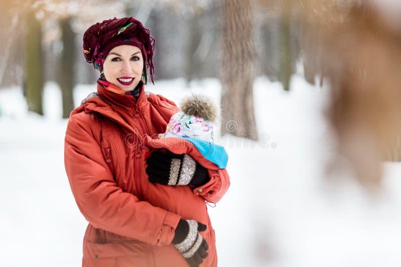 La madre que lleva a su bebé lleva la chaqueta y la honda rojas fotografía de archivo