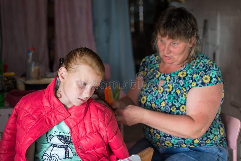 La madre que pone en trenzas en su hija y ese algo dice seriamente imagen de archivo libre de regalías