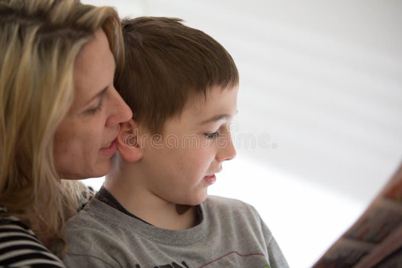 La madre rubia y el muchacho moreno se sienta juntos, y disfruta de lectura interior Luz natural imagenes de archivo