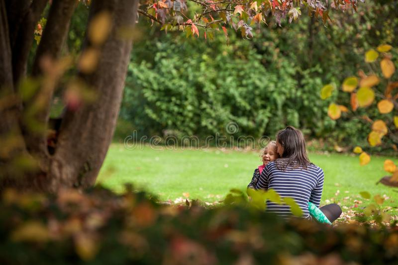 La madre se está divirtiendo con la hija en el parque en otoño, muchacha rizada linda rubia, familia feliz imagen de archivo