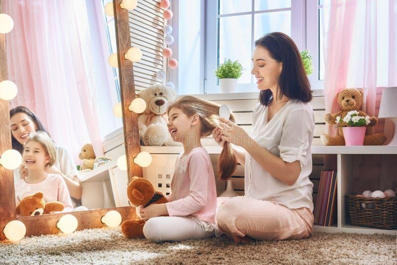 La madre se está peinando el pelo del ` s de la hija fotos de archivo libres de regalías