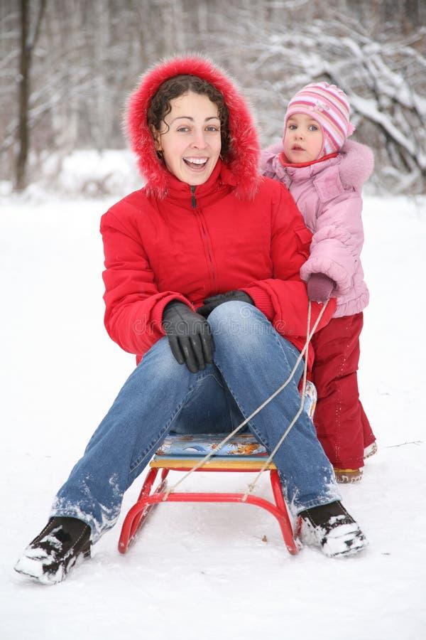 La madre se sienta en el trineo con el niño fotografía de archivo
