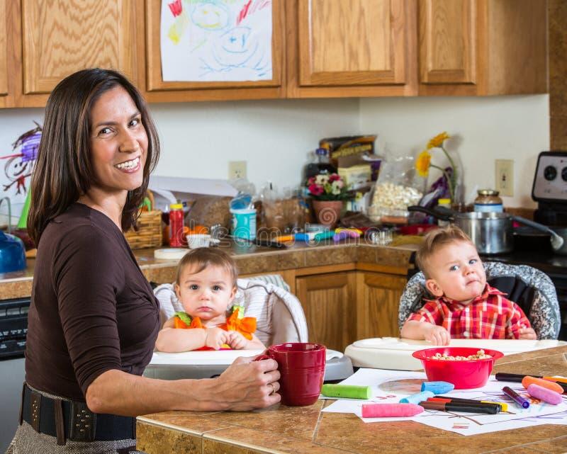 La madre sonríe con los bebés imagenes de archivo