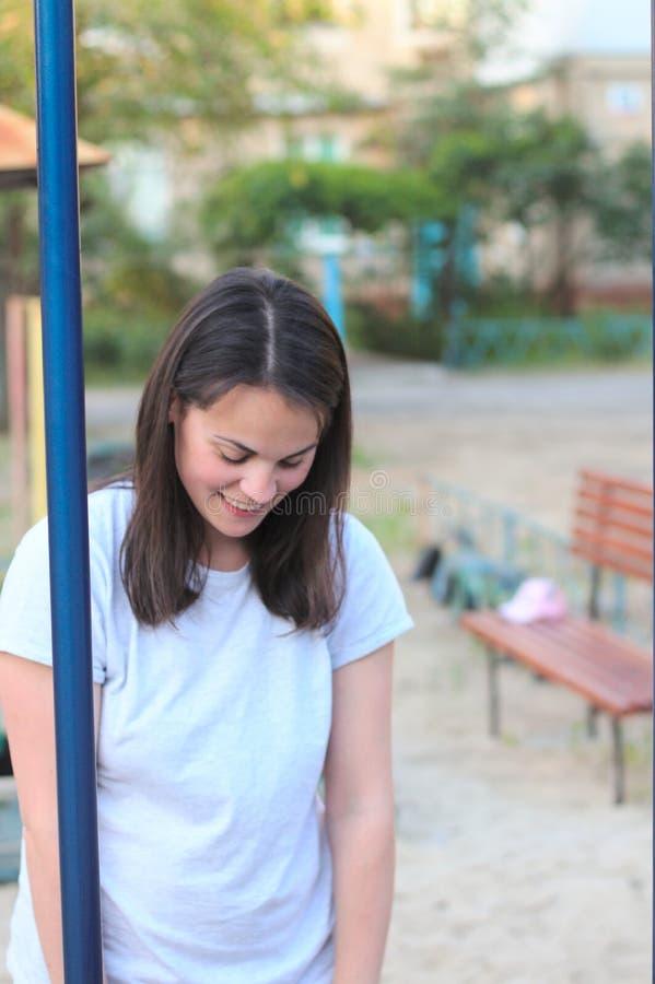 la madre sonriente en una camiseta blanca con el pelo marrón largo mira abajo el niño en el patio fotos de archivo libres de regalías