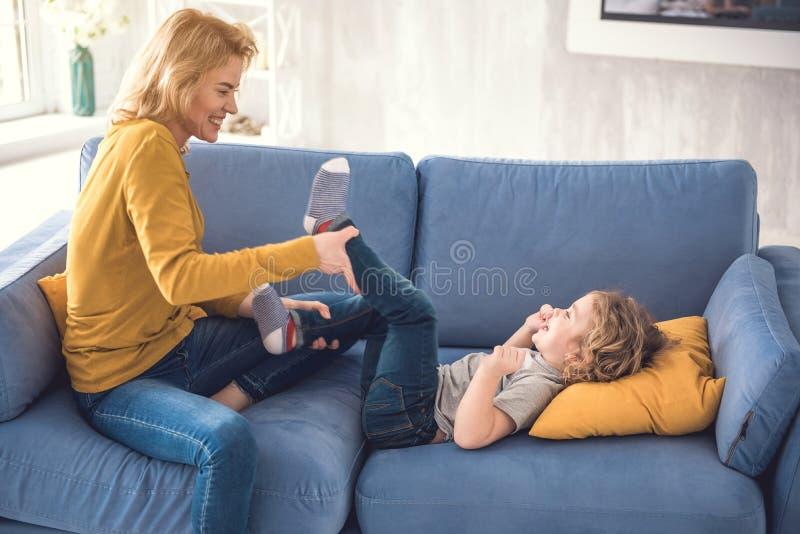 La madre sorridente sta incitando il bambino a ridere all'interno fotografia stock