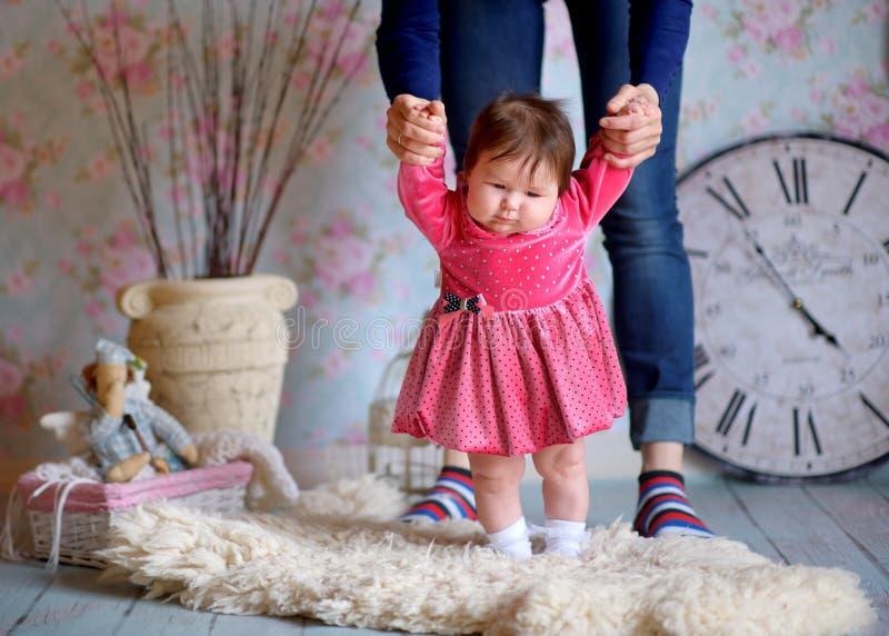La madre sostiene con attenzione a mano la piccola figlia immagini stock