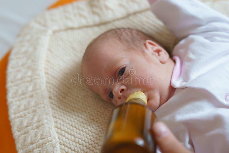 La madre sta alimentando la ragazza neonata con il biberon immagini stock libere da diritti