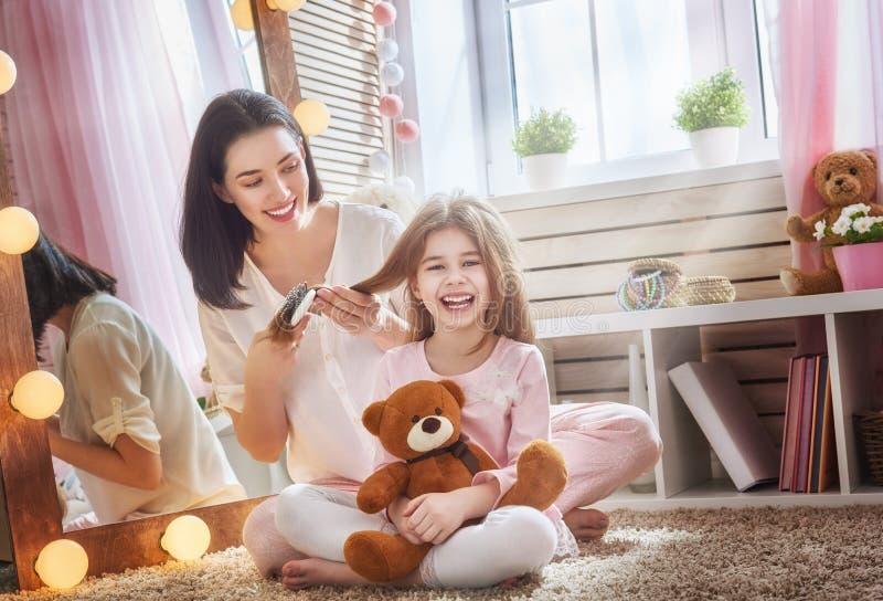 La madre sta pettinando i suoi capelli del ` s della figlia immagine stock