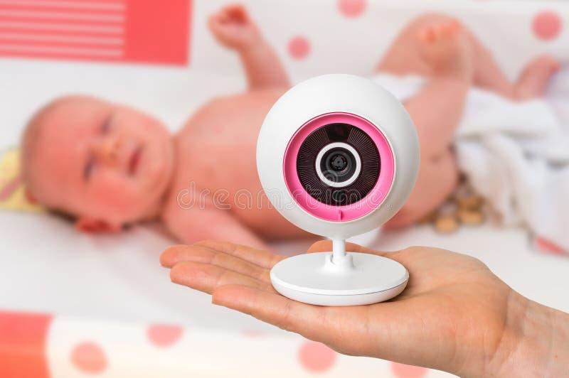 La madre sta tenendo la macchina fotografica del monitor del bambino per la sicurezza del suo bambino fotografia stock libera da diritti