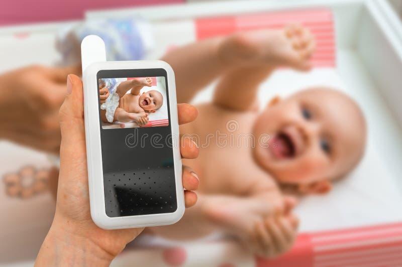 La madre sta tenendo la macchina fotografica del monitor del bambino per la sicurezza del suo bambino fotografie stock libere da diritti