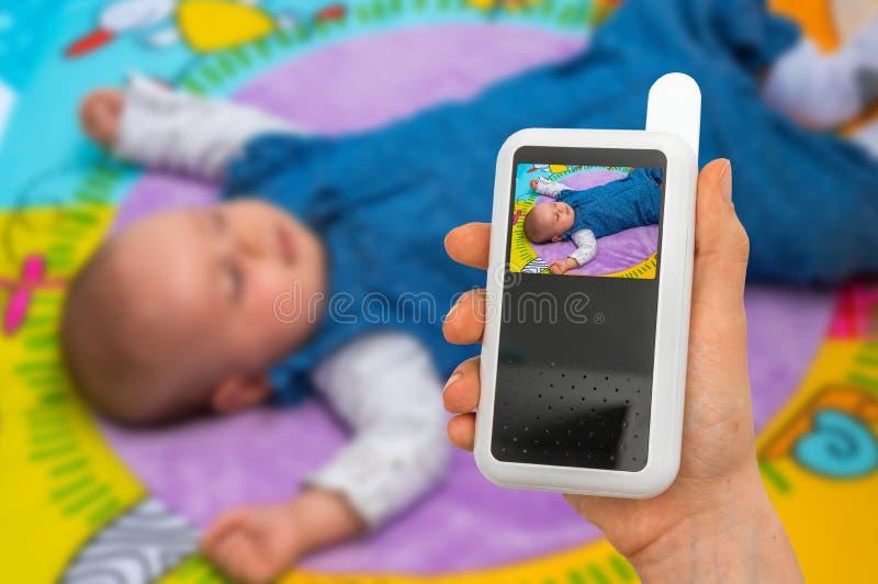 La madre sta tenendo la macchina fotografica del monitor del bambino per la sicurezza del suo bambino immagini stock libere da diritti