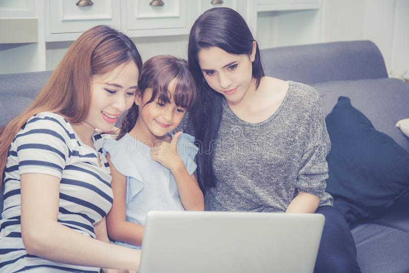La madre, la tía y el niño teniendo tiempo juntos lerning con usar el ordenador portátil en casa con se relajan y feliz fotos de archivo