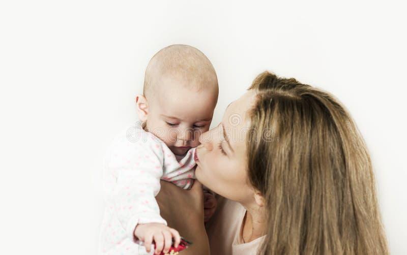 La madre tiene il bambino nelle sue armi su fondo isolato immagini stock libere da diritti