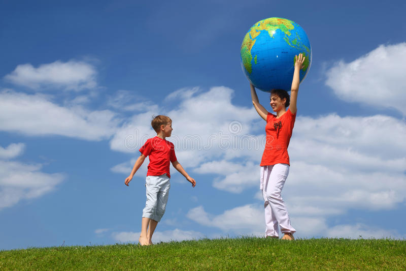 La madre tiene la sfera di mani, ragazzo viene funzionando ad esso immagini stock