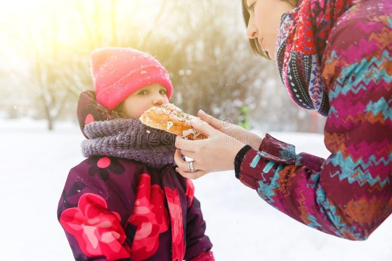 La madre trata a la hija con el rollo foto de archivo libre de regalías