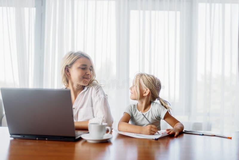 La madre utiliza el ordenador portátil en casa, niño la mira fotos de archivo