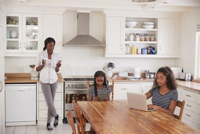 La madre utiliza el teléfono como hijas Sit At Table Doing Homework fotografía de archivo libre de regalías