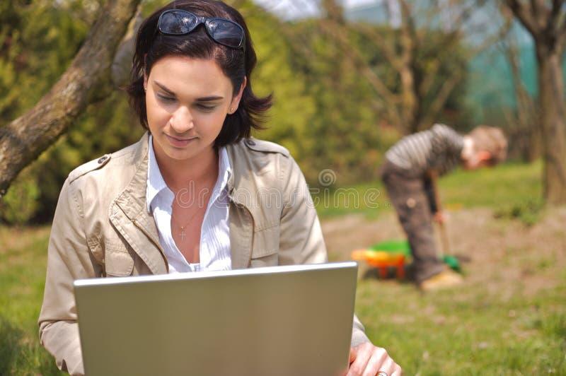 La madre utiliza una computadora portátil fotos de archivo libres de regalías