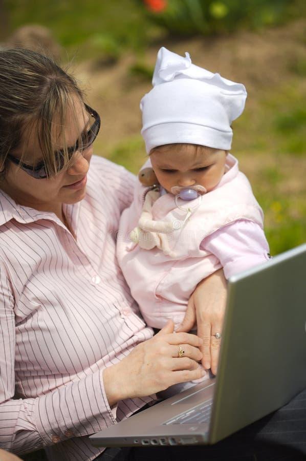 La madre utiliza una computadora portátil imagen de archivo