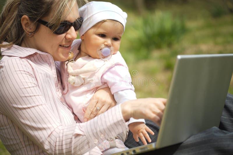 La madre utiliza una computadora portátil imagen de archivo libre de regalías