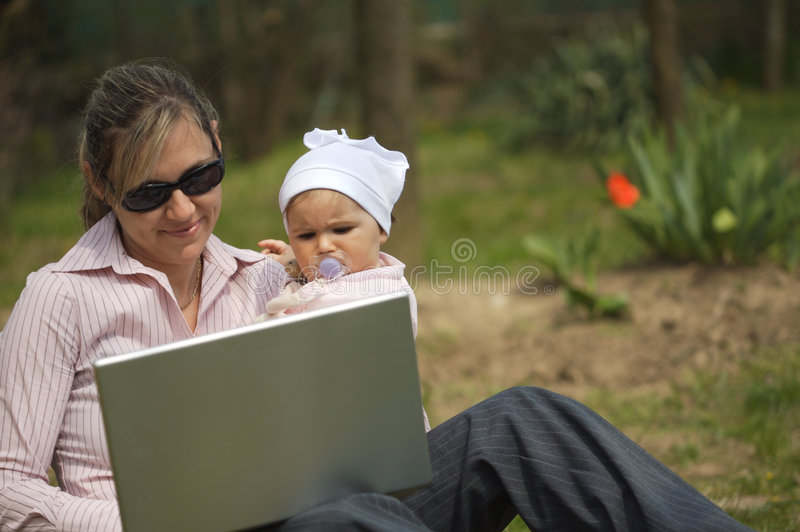 La madre utiliza una computadora portátil fotos de archivo