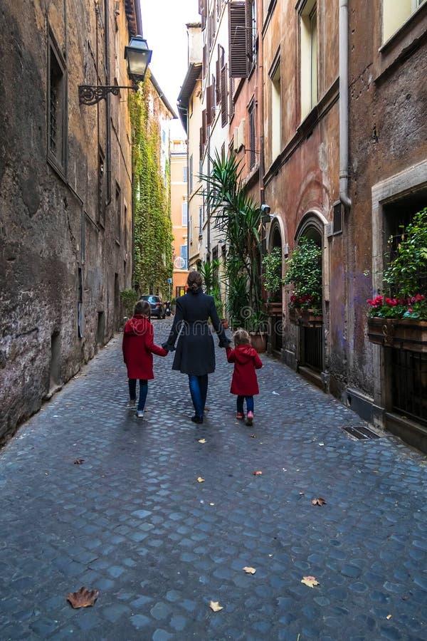 La madre y dos hijas caminan en la ciudad europea vieja foto de archivo